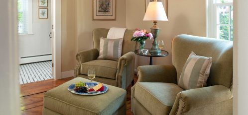 A section of the seating area with olive green chairs in The Wellfleet Room at The Inn at Yarmouth Port