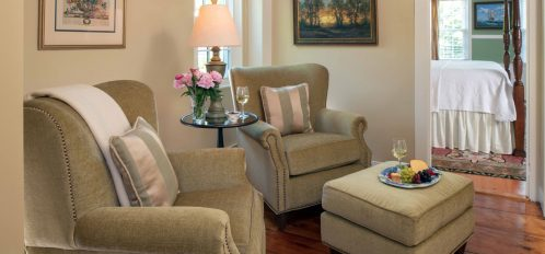 another view of the seating area with olive green chairs in The Wellfleet Room at The Inn at Yarmouth Port